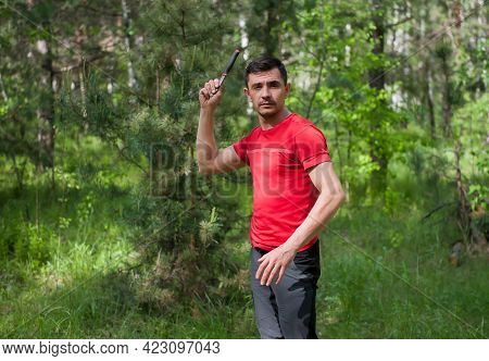 A Man Throws A Knife At A Target In The Summer Forest, Front View. Throwing A Knife