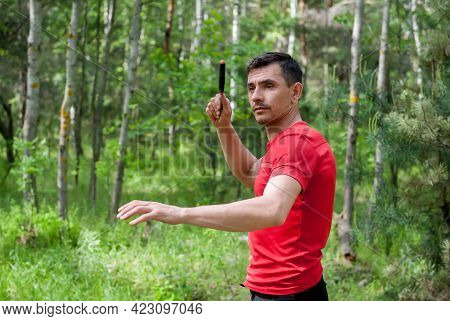A Man Throws A Knife At A Target In The Summer Forest. Throwing A Knife