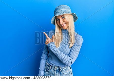 Young blonde woman wearing casual denim hat cheerful with a smile of face pointing with hand and finger up to the side with happy and natural expression on face