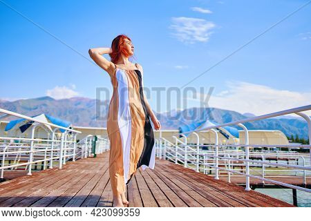 Pretty Woman Enjoying The Vacation. Marine Wooden Pier With Umbrellas. Hot Summer Day. Walk By The O