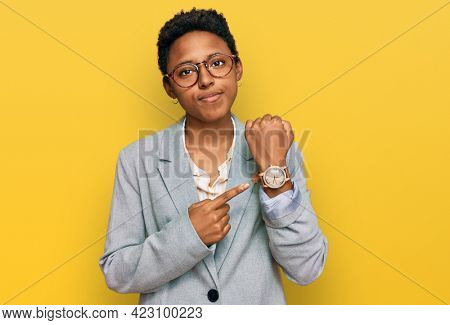 Young african american woman wearing business clothes in hurry pointing to watch time, impatience, looking at the camera with relaxed expression