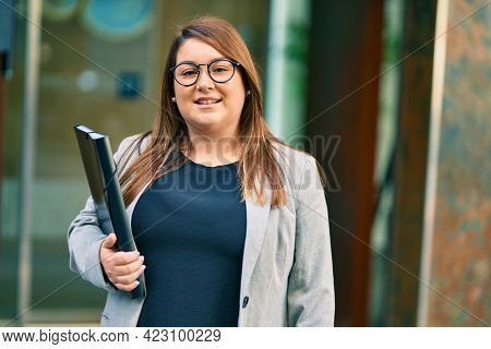 Young hispanic plus size businesswoman smiling happy holding binder at the city.