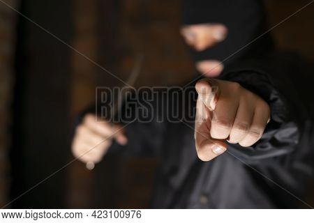 Close Up, The Finger Of A Bandit, Terrorist, Criminal In A Black Mask, With Which He Points At The V