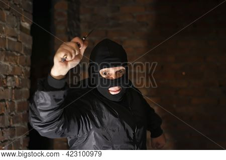 A Bandit, Terrorist, Criminal In A Black Mask Attacks With A Knife In His Hand In A Dark Room Of An