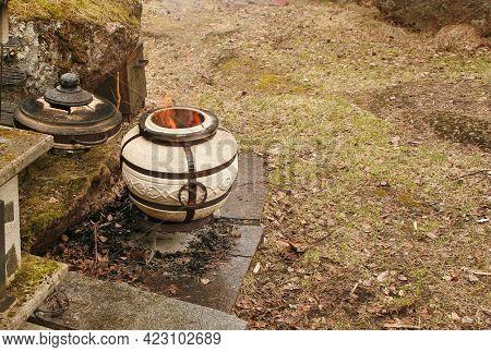 Burning Tandoor Stands On The Grass. Smoking Tandoor.