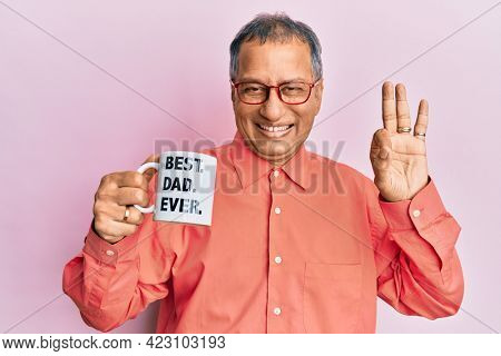 Middle age indian man drinking mug of coffee with best dad ever message doing ok sign with fingers, smiling friendly gesturing excellent symbol