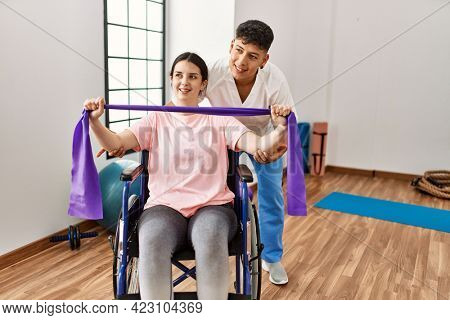 Young disabled woman sitting on wheelchair making mobility exercise using elastic band at the clinic.