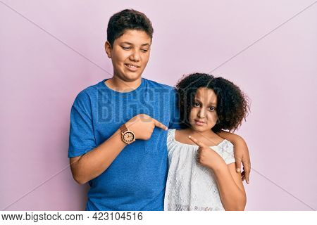 Young hispanic family of brother and sister wearing casual clothes together pointing aside worried and nervous with forefinger, concerned and surprised expression