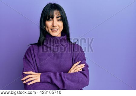 Young brunette woman with bangs wearing turtleneck sweater happy face smiling with crossed arms looking at the camera. positive person.