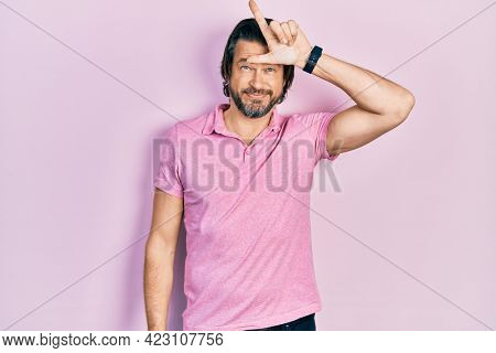Middle age caucasian man wearing casual white t shirt making fun of people with fingers on forehead doing loser gesture mocking and insulting.