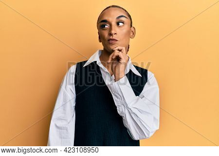 Hispanic man wearing make up and long hair wearing fashion clothes thinking concentrated about doubt with finger on chin and looking up wondering