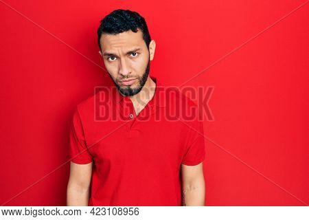 Hispanic man with beard wearing casual red t shirt skeptic and nervous, frowning upset because of problem. negative person.