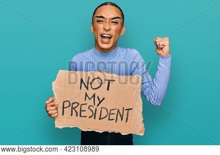 Hispanic transgender man wearing make up and long hair holding not my president protest banner annoyed and frustrated shouting with anger, yelling crazy with anger and hand raised