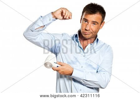 one caucasian man with sweat stain perspire drying shirt with hair dryer in studio isolated on white background