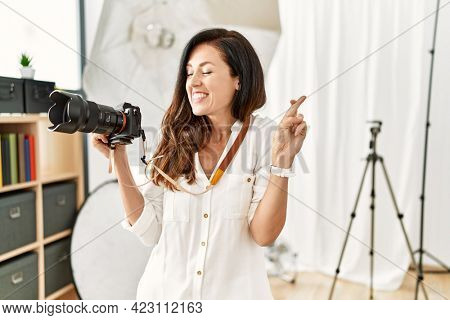 Beautiful caucasian woman working as photographer at photography studio gesturing finger crossed smiling with hope and eyes closed. luck and superstitious concept.