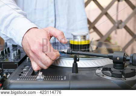 The Dj Adjusts The Stylus On The Turntable. Hand Of A Male Dj In A Blue Shirt. Unrecognizable Young