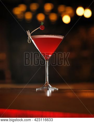 Red Alcoholic Cocktail Decorated With Berry At Wooden Table. Transparent Glass Of Alcoholic Drink Is