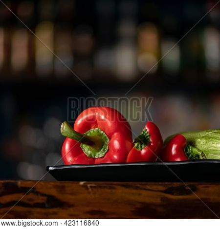Fresh Vegetables. Red Bell Pepper, Capsicum Or Paprika And Zucchini On Black Blurred Background. Org