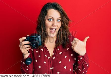 Young caucasian woman holding reflex camera pointing thumb up to the side smiling happy with open mouth
