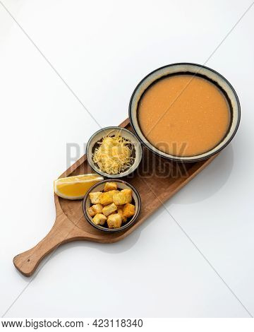 Orange Cream Soup. Pumpkin Or Lentil Soup Garnished With Grated Cheese And Croutons On Wooden Cuttin
