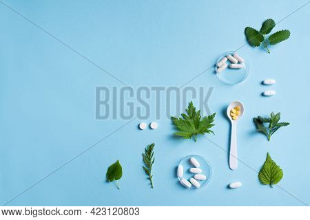 Homeopathy, Naturopathy And Alternative Herbal Medicine. Capsules And Pills, Green Plant Leaves On B
