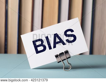 A White Card With The Text Bias Stands On A Clip For Papers On The Table Against The Background Of B