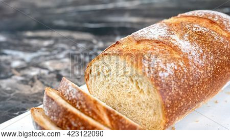 Closeup Of A Partially Sliced Loaf Of Homemade Artisan Wheat Bread, With Crunchy Crust And Open Crum