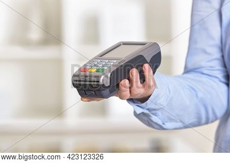 A hand holding a wireless card payment terminal at shop