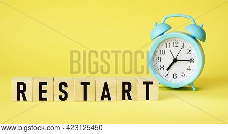 Concept Of The Word Restart On Cubes On A Yellow Background With An Alarm Clock .business Concept. C