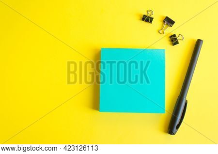Square Sheet Of Paper For Notes. Blue Sheet Of Paper, Black Permanent Liner, Paper Clips. Copy Space
