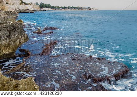 Shoreline Rocks Washing By Mediterranean Sea Waves. Water Are Blurred To Show Its Movement. Building