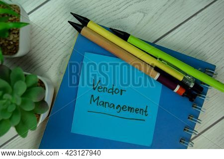 Vendor Management Write On Sticky Notes Isolated On Wooden Table.