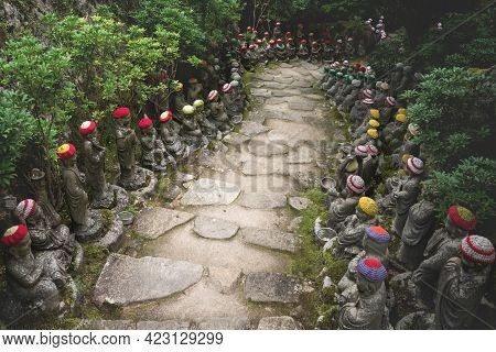 Stone Path Surrounded By Buddha Statues With Knitted Hat Offerings Representing The First 500 Discip