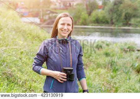Young Woman Standing With Binoculars Near The Pond