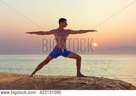 Young Man Practicing Yoga At The Seashore