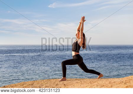 Young Fitness Woman Practicing Yoga At The Seashore In The Morning