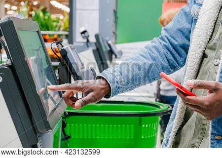The Finger Of An African Man In Close-up At The Supermarket Checkout Selects The Desired Product On