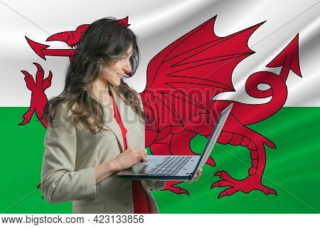 Freelance In Wales. Beautiful Young Woman Freelancer Uses Laptop Computer Against The Background Of