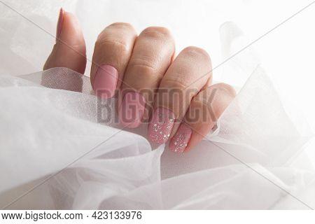 Soft Pink Varnish And Sparkles On Nails - Gel Varnish Salon Coating Manicure.