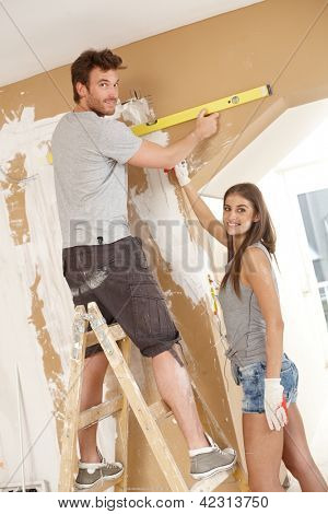 Attractive young couple building new home using spirit level to measure.