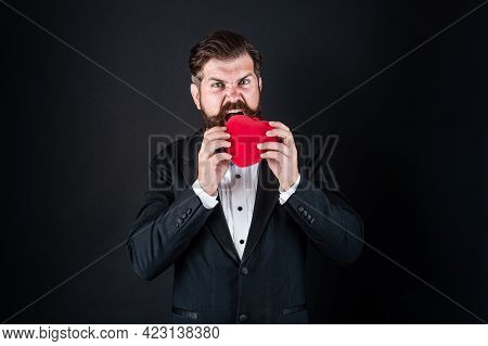 Handsome Man In Tuxedo Biting Or Eating Love Heart For Valentines Day, Heartbreaker