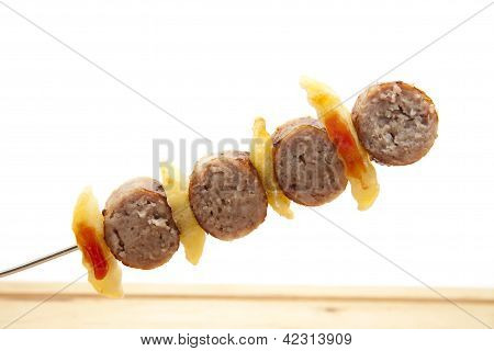 Meatballs with Chips Frites on Metal Spit