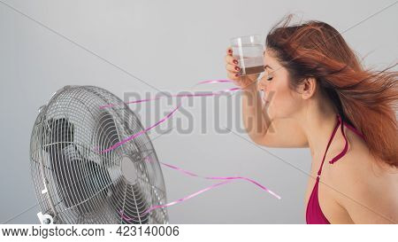Red-haired Caucasian Woman In A Bikini Drinks A Cool Drink And Enjoys The Blowing Wind From An Elect