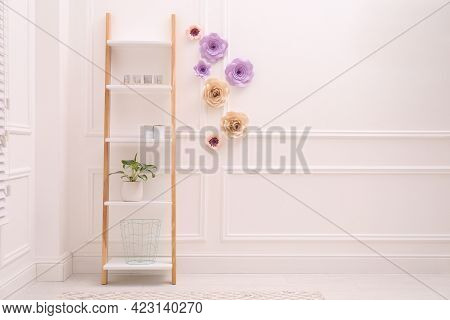 Shelving Unit Near Wall With Floral Decor In Room, Space For Text. Interior Design