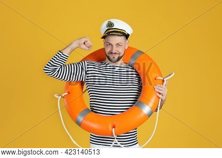 Sailor With Orange Ring Buoy Showing Biceps On Yellow Background
