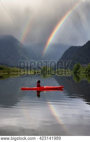 Adventure Caucasian Adult Woman Kayaking In Red Kayak Surrounded By Canadian Mountain Landscape. Rai