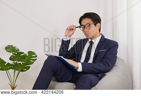 Asian Financial Advisor Wear Glasses Headache With Financial Statement In Home Office.businessman Wo