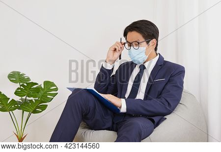 Asian Financial Advisor Wear Mask Touch Glasses And Thinking In Home Cafe Office. Businessman Work A