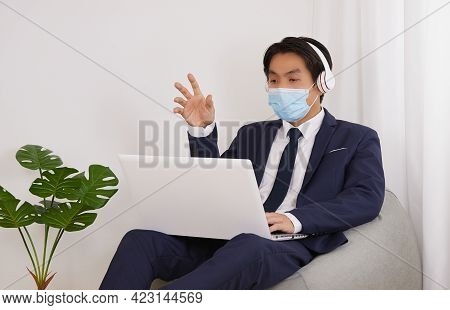 Asian Financial Advisor Wear Mask And Headphone Video Conference With Customer In Home Cafe Office.