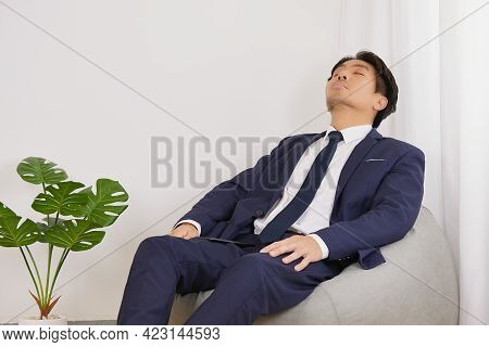 Asian Businessman In Suit Rest His Eyes Or Nap Or Sleep On Bean Bag In Home Office. Rest Time Of Bus